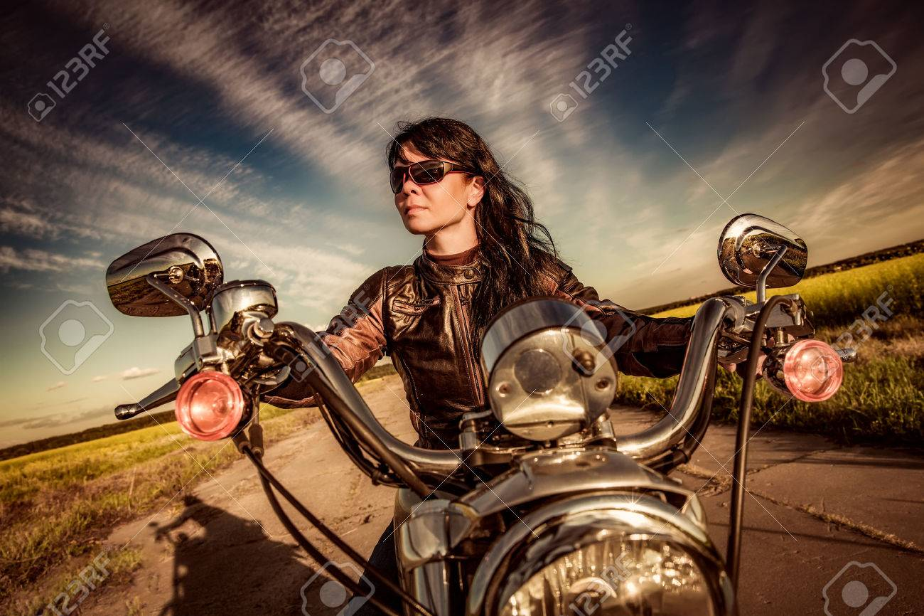 Biker girl in a leather jacket on a motorcycle - 53105933