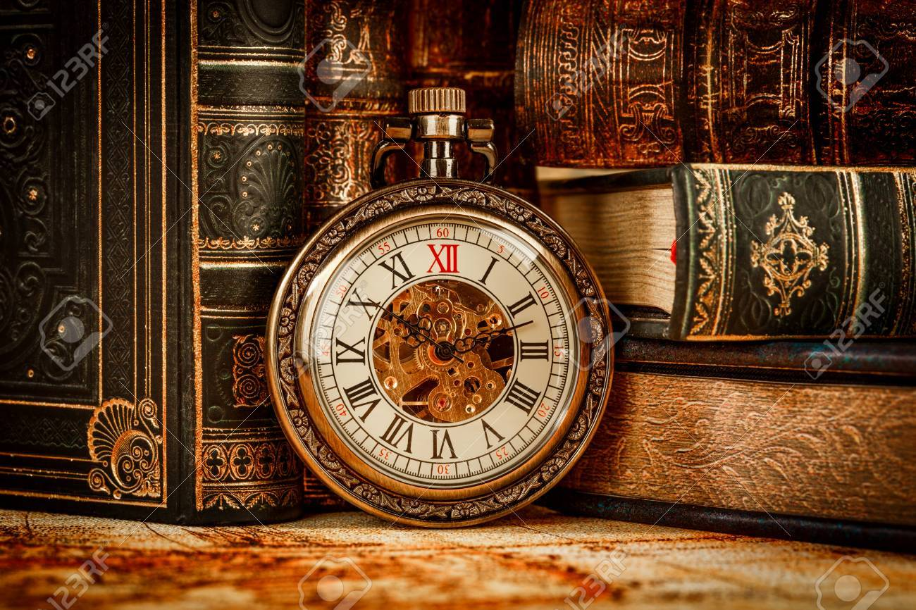 vintage antique pocket watch on the background of old books stock
