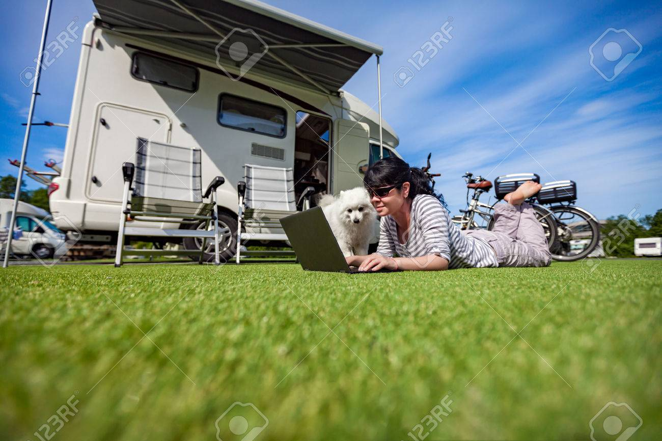 Woman on the grass with a dog looking at a laptop. Caravan car Vacation. Family vacation travel, holiday trip in motorhome - 62009824