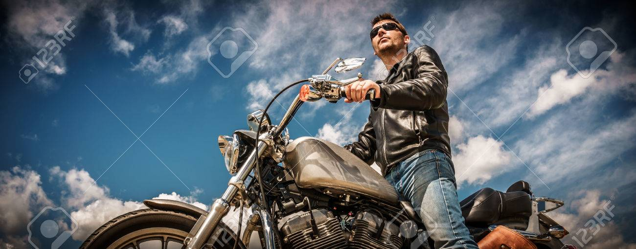 Biker man wearing a leather jacket and sunglasses sitting on his motorcycle. - 64786775