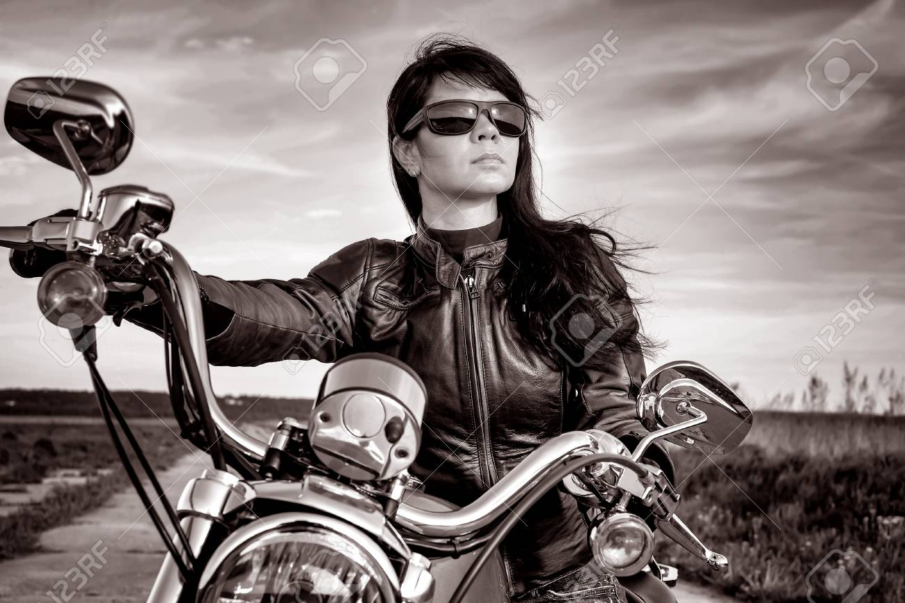 Biker girl in a leather jacket on a motorcycle in black and white stock photo