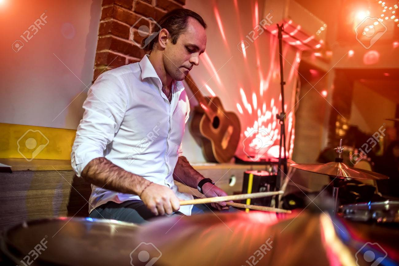 Drummer playing on drum set on stage. Warning - authentic shooting with high iso in challenging lighting conditions. A little bit grain and blurred motion effects. Stock Photo - 75712977