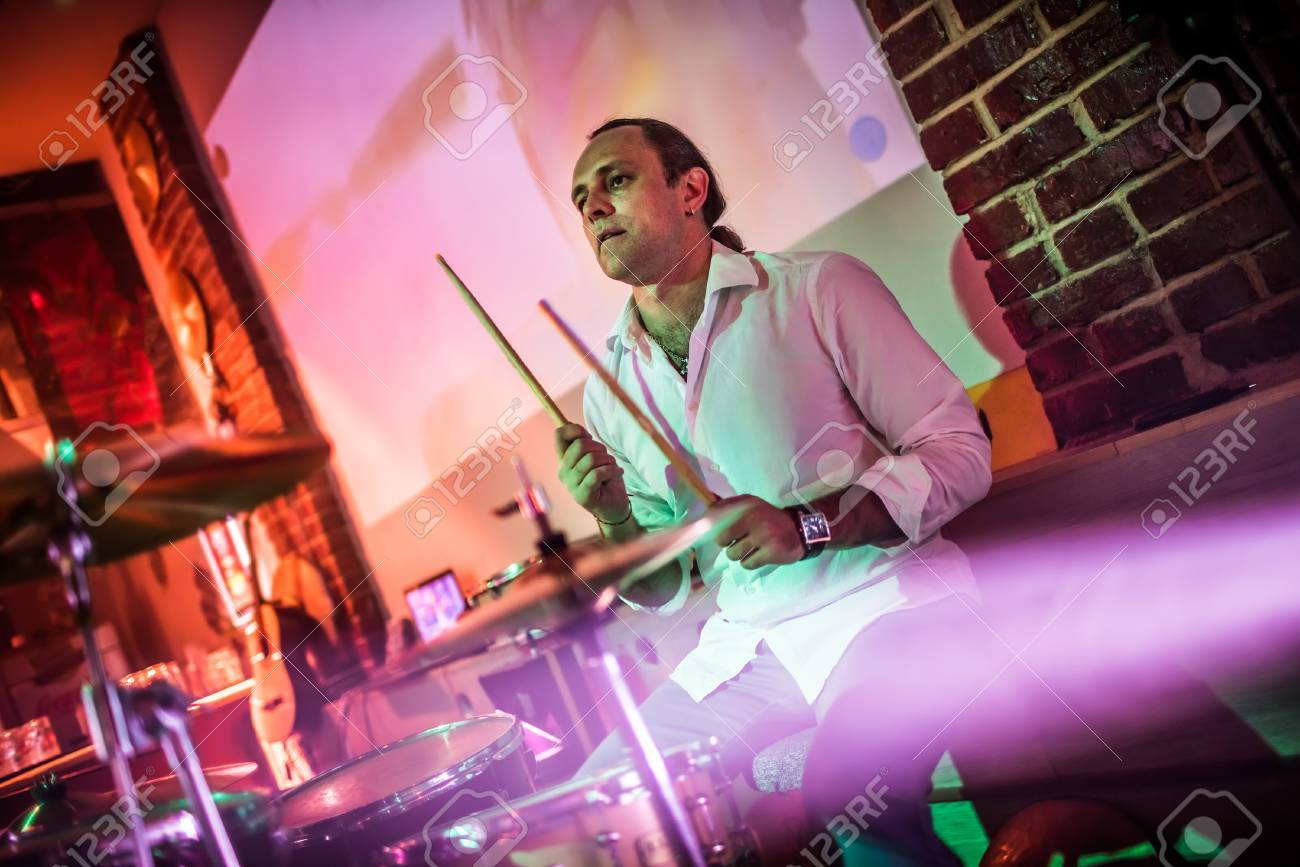 Drummer playing on drum set on stage. Warning - authentic shooting with high iso in challenging lighting conditions. A little bit grain and blurred motion effects. Stock Photo - 75713088