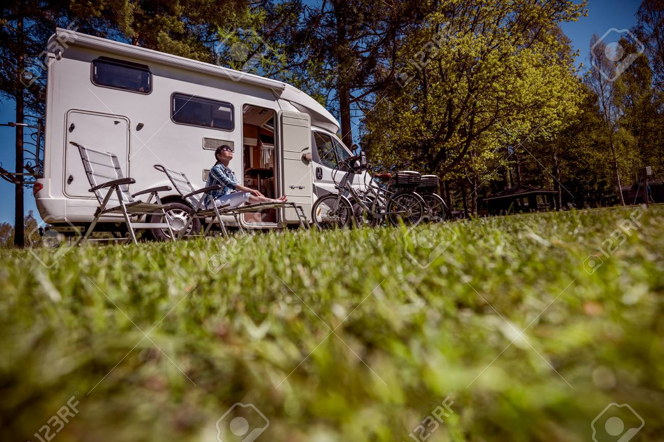 Woman resting near motorhomes in nature. Family vacation travel, holiday trip in motorhome RV, Caravan car Vacation. - 93697125