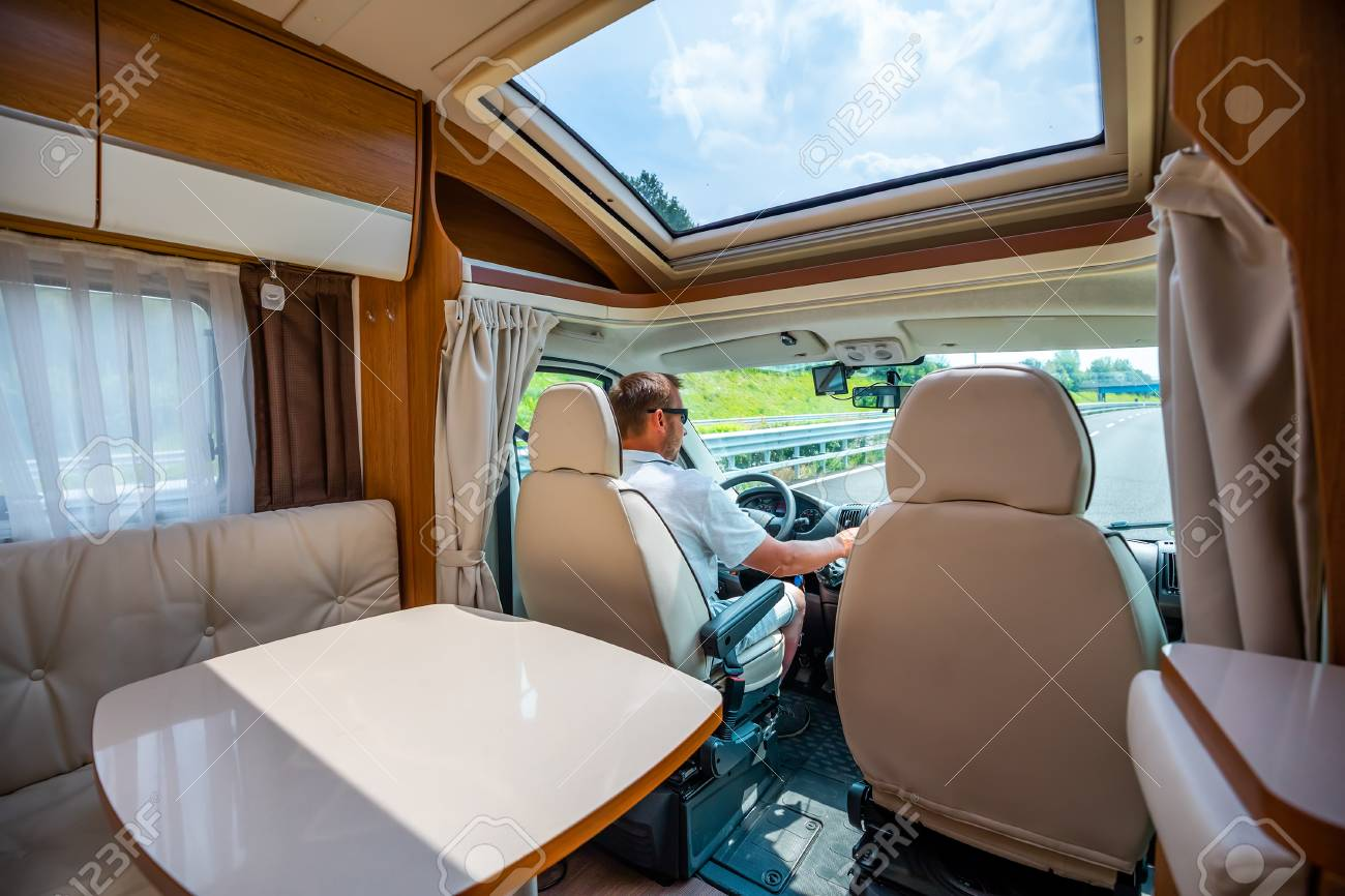 Man driving on a road in the Camper Van RV. Caravan car Vacation. Family vacation travel, holiday trip in motorhome - 107320810