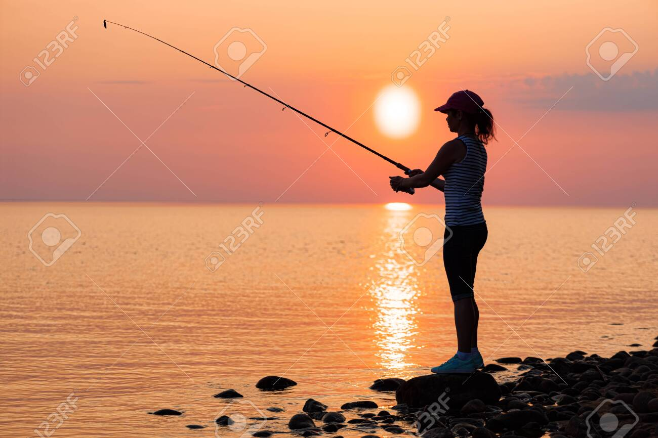 Woman fishing on Fishing rod spinning at sunset background. - 146032891