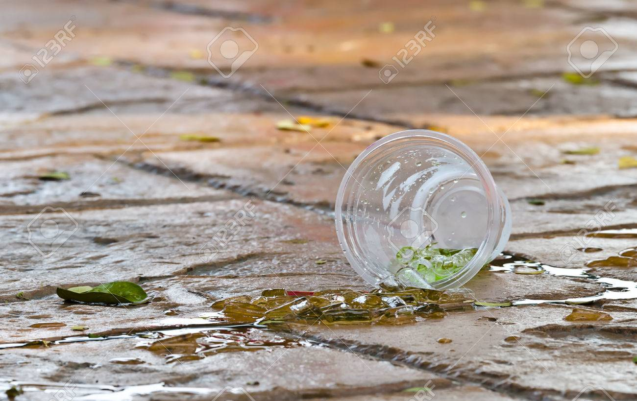Plastic Cup Of Drinking Water And Ice Drop On The Floor Stock Photo