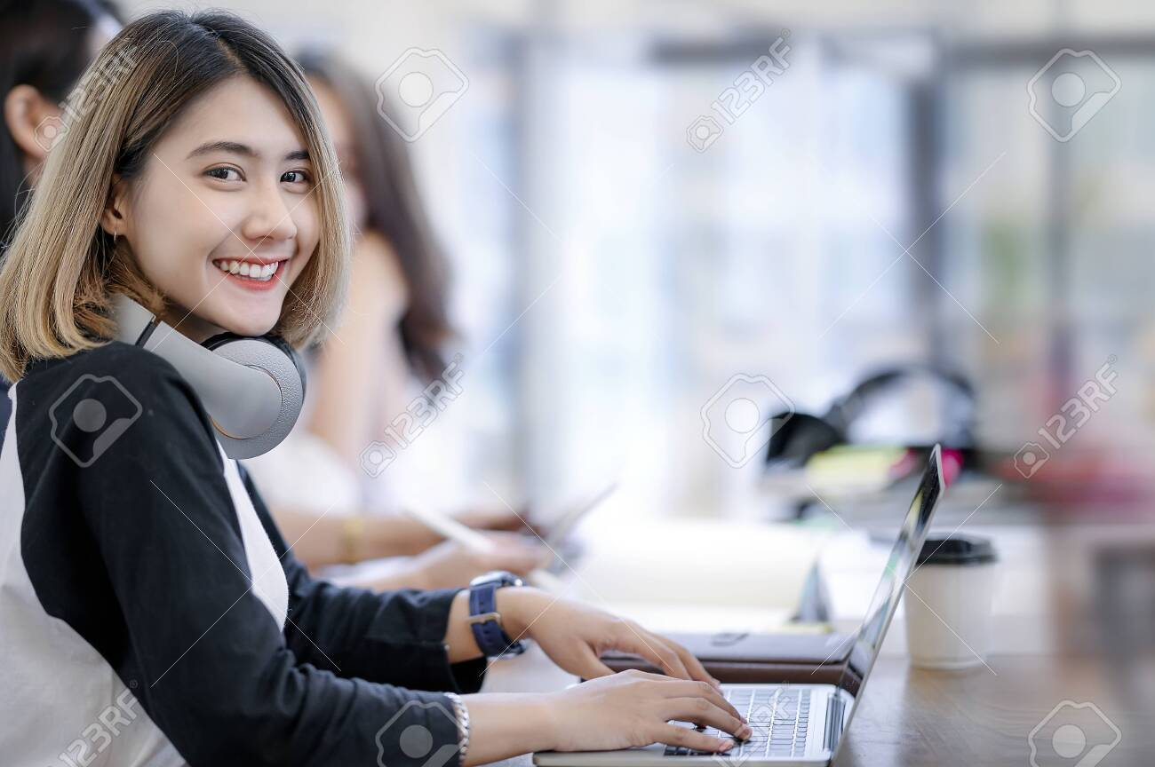 Portrait of young woman smiling and looking at camera while working in modern office with her friends. - 131818607