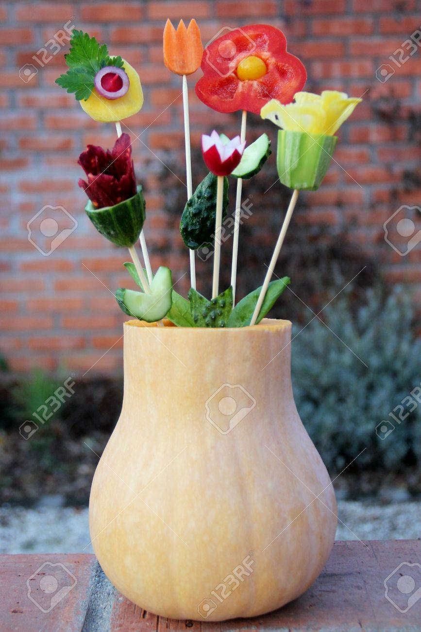 Nosegay from different vegetables in a pumpkin vase Stock Photo - 24600925