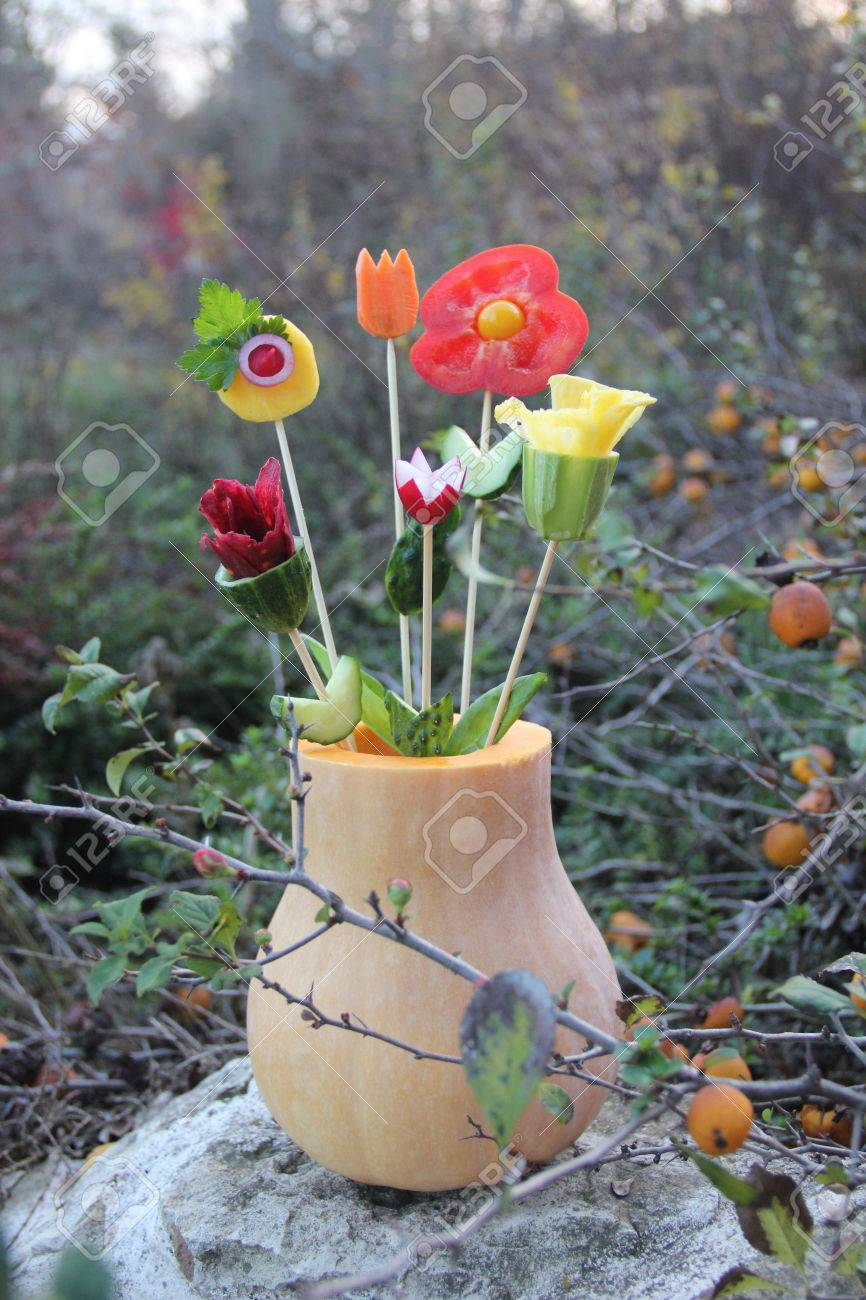 Flowers from vegetables in a pumpkin vase, outdoor Stock Photo - 24600928