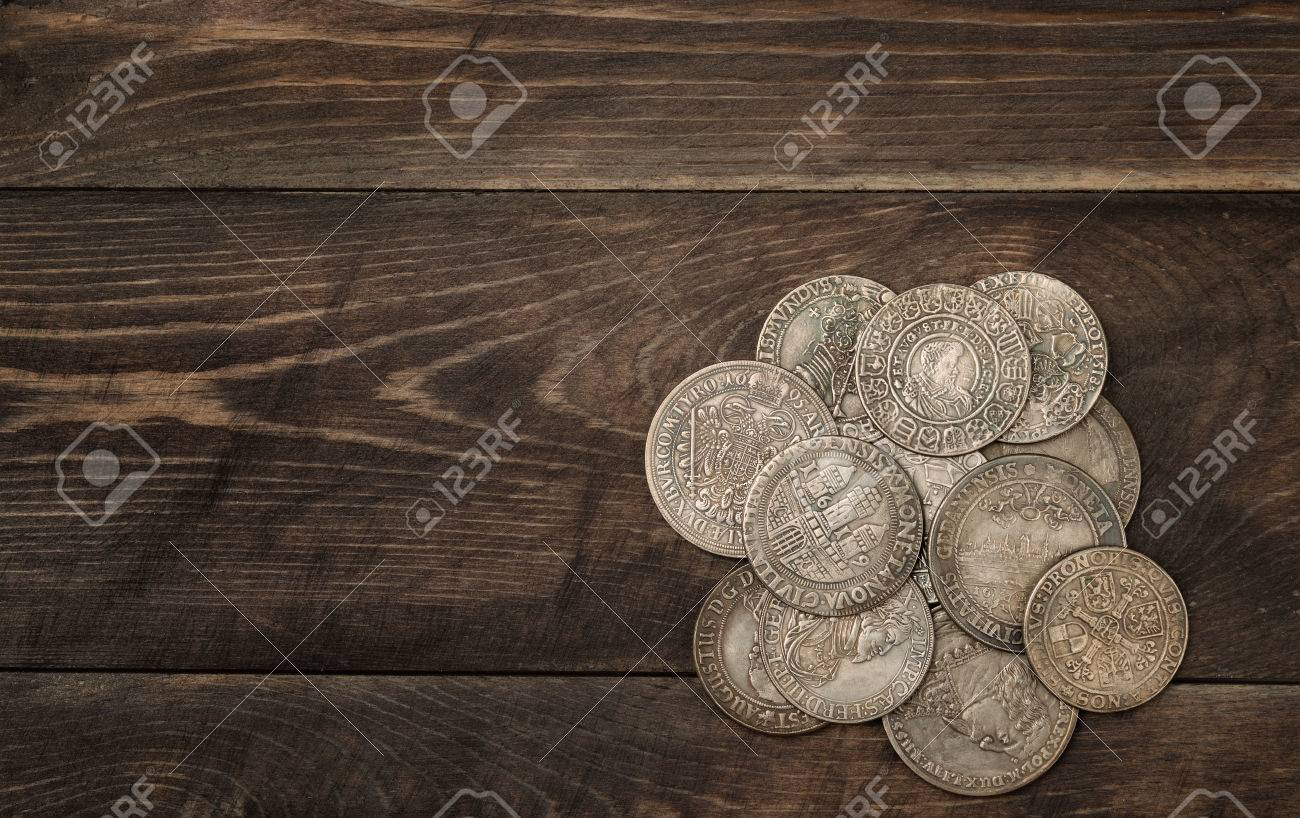 Ancient silver coins on dark wooden background - 55758298