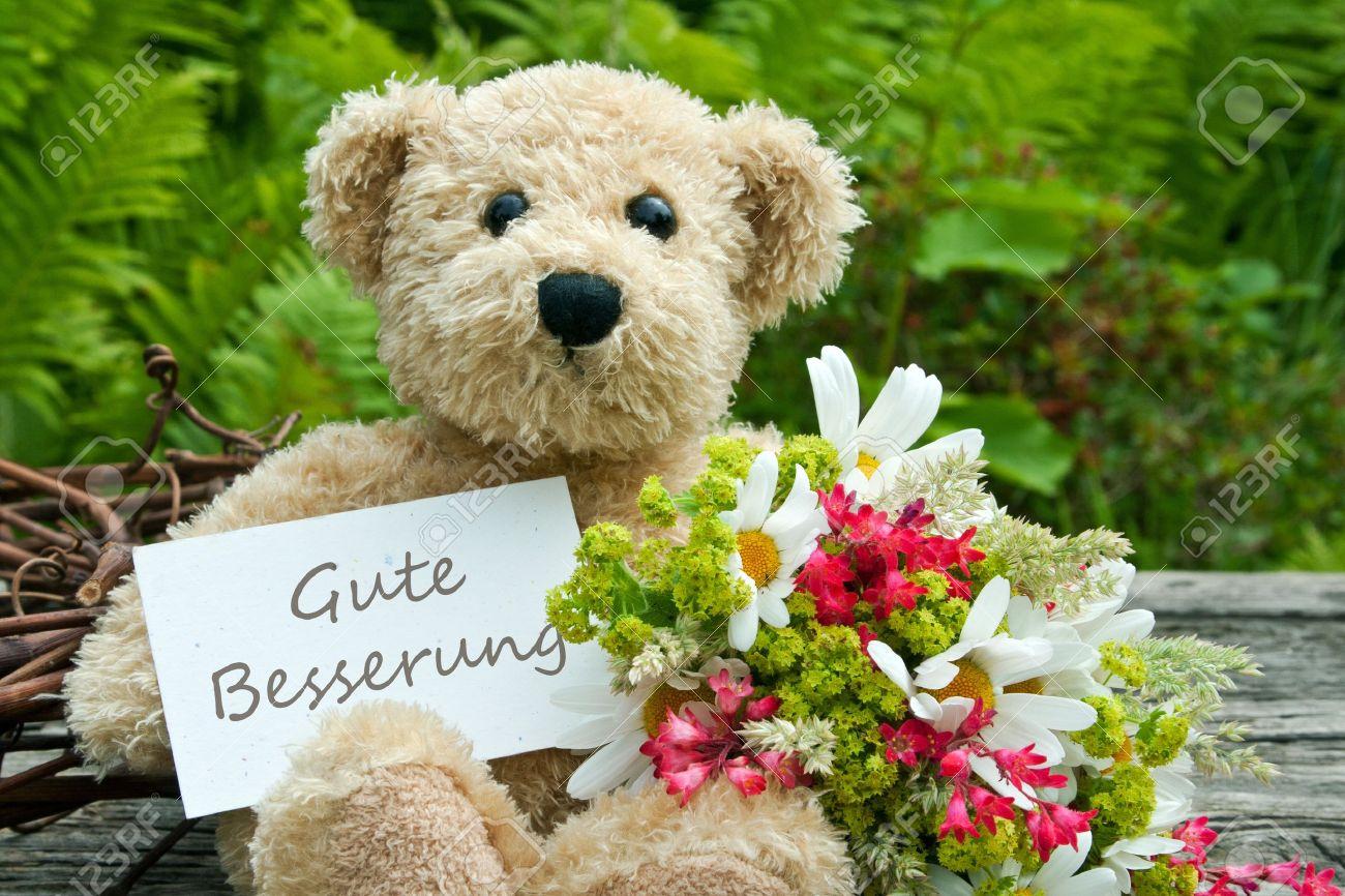 Teddybär mit Blumen und Karte mit Schriftzug get well Standard-Bild - 21133191