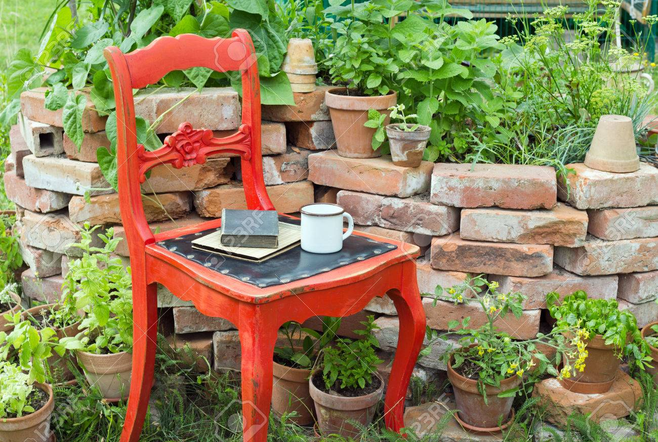 red chair in a garden with herbs, cup and books Standard-Bild - 29835999