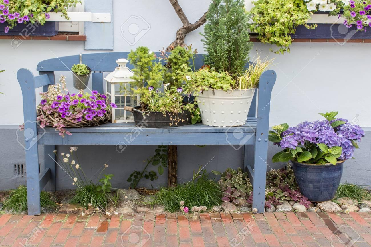 Decorazioni Da Giardino : Banco da giardino blu davanti alla casa con fiori e decorazioni