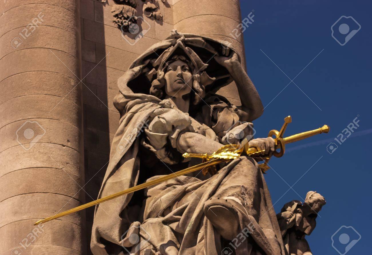 sculpture of a woman holding a golden sword - 19877108