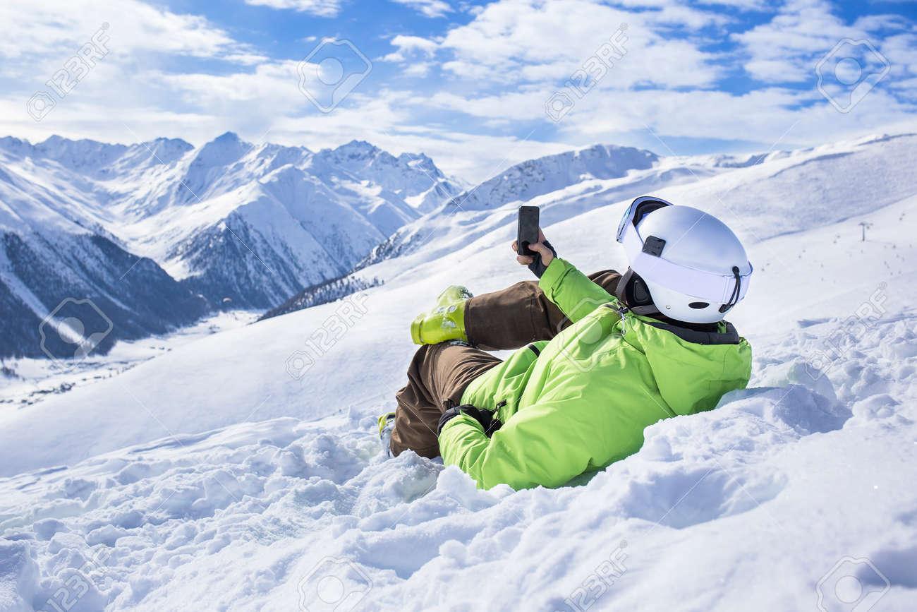 Happy successful man surfing mobile phone app at apine ski slope livigno italy resort village - 48360407