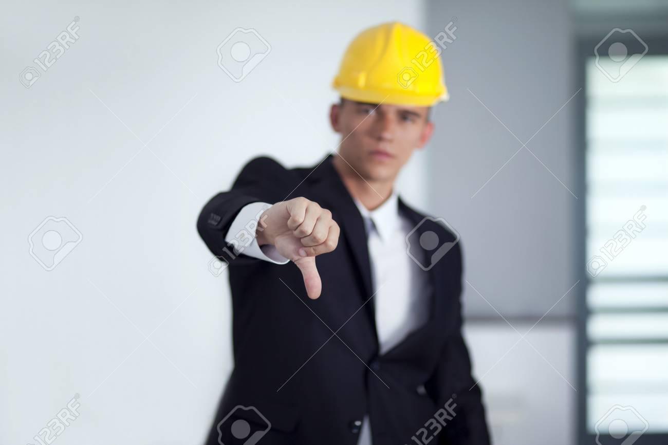 ed4871175fa9 Banque d images - Homme d affaires prospère avec des poses de casques  jaunes et les pouces des gestes de la main vers le bas