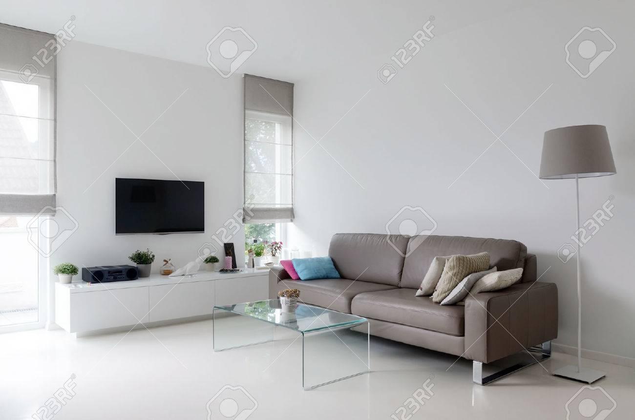 Vit vardagsrum med taupe skinnsoffa och glasbord royalty fria ...