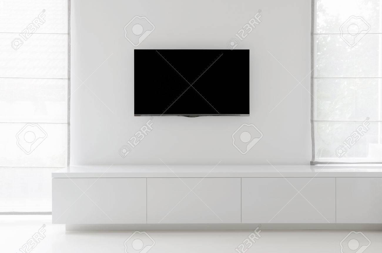 Witte woonkamer detail tv aan de muur met commode en epoxy vloeren ...