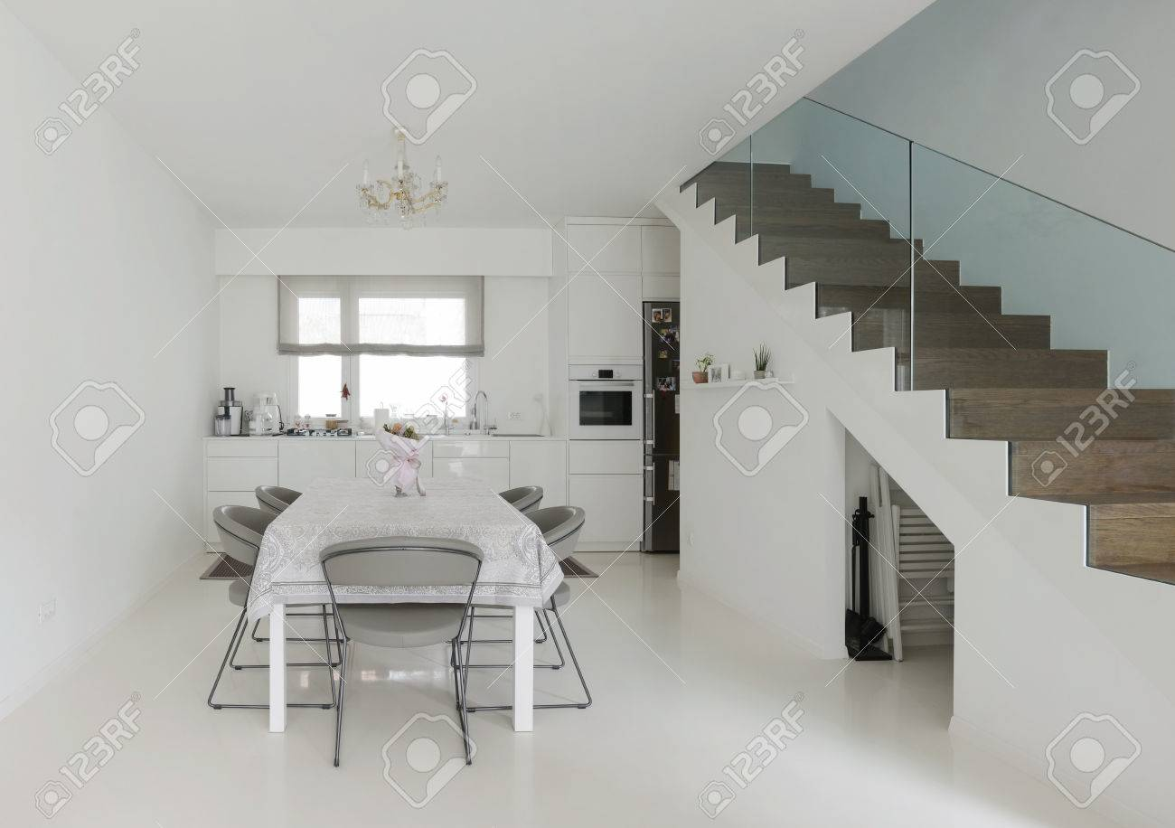 White Kitchen And Dining Room With Epoxy Floor Stock Photo