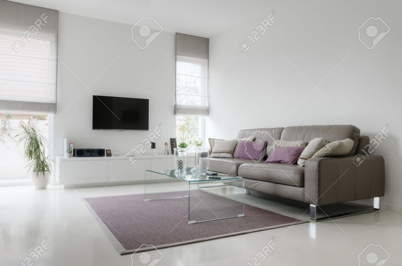 Stock photo white living room with taupe leather sofa and glass table on carpet