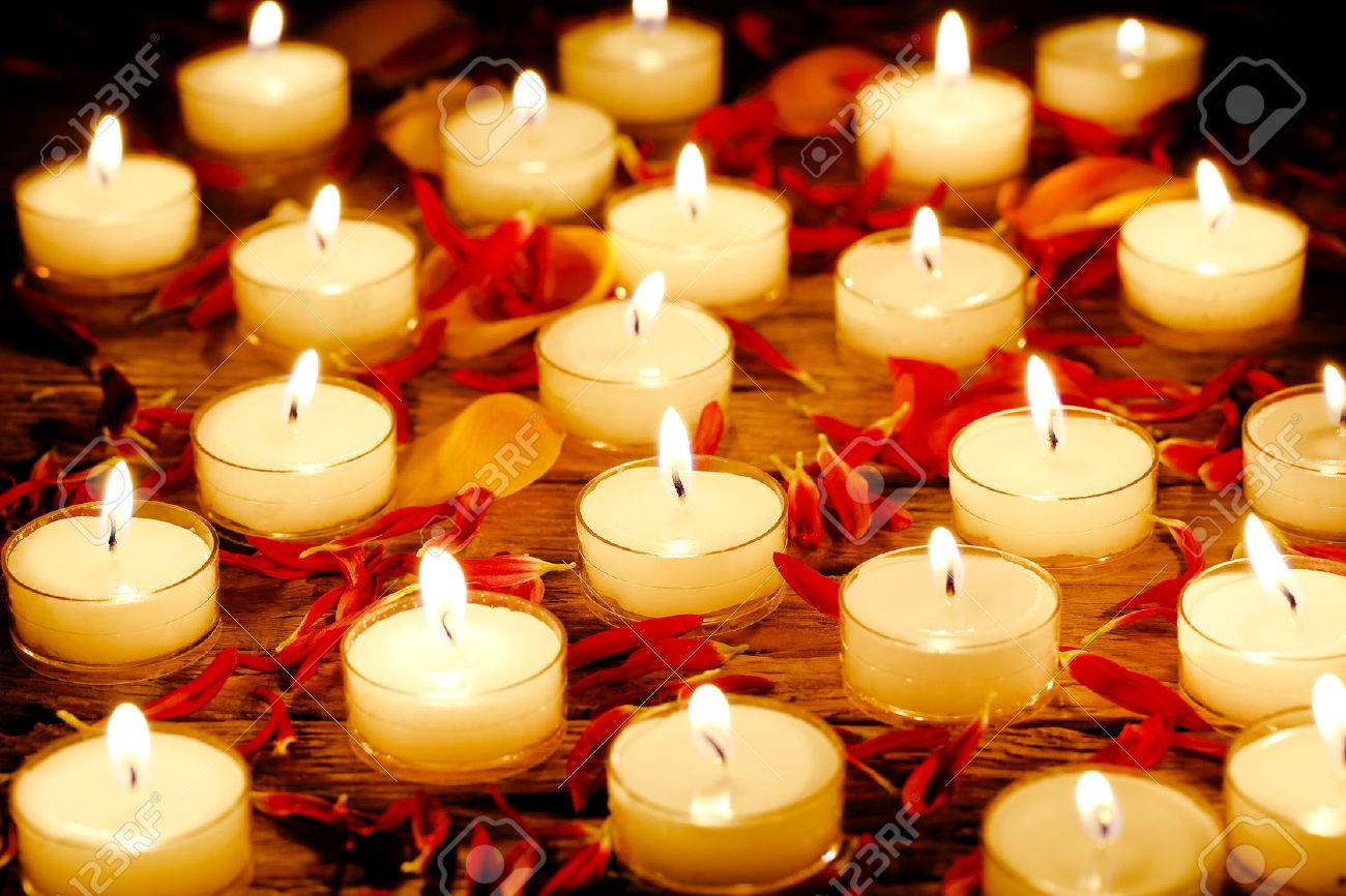 burning candles with flower petals on wooden surface - 48128367