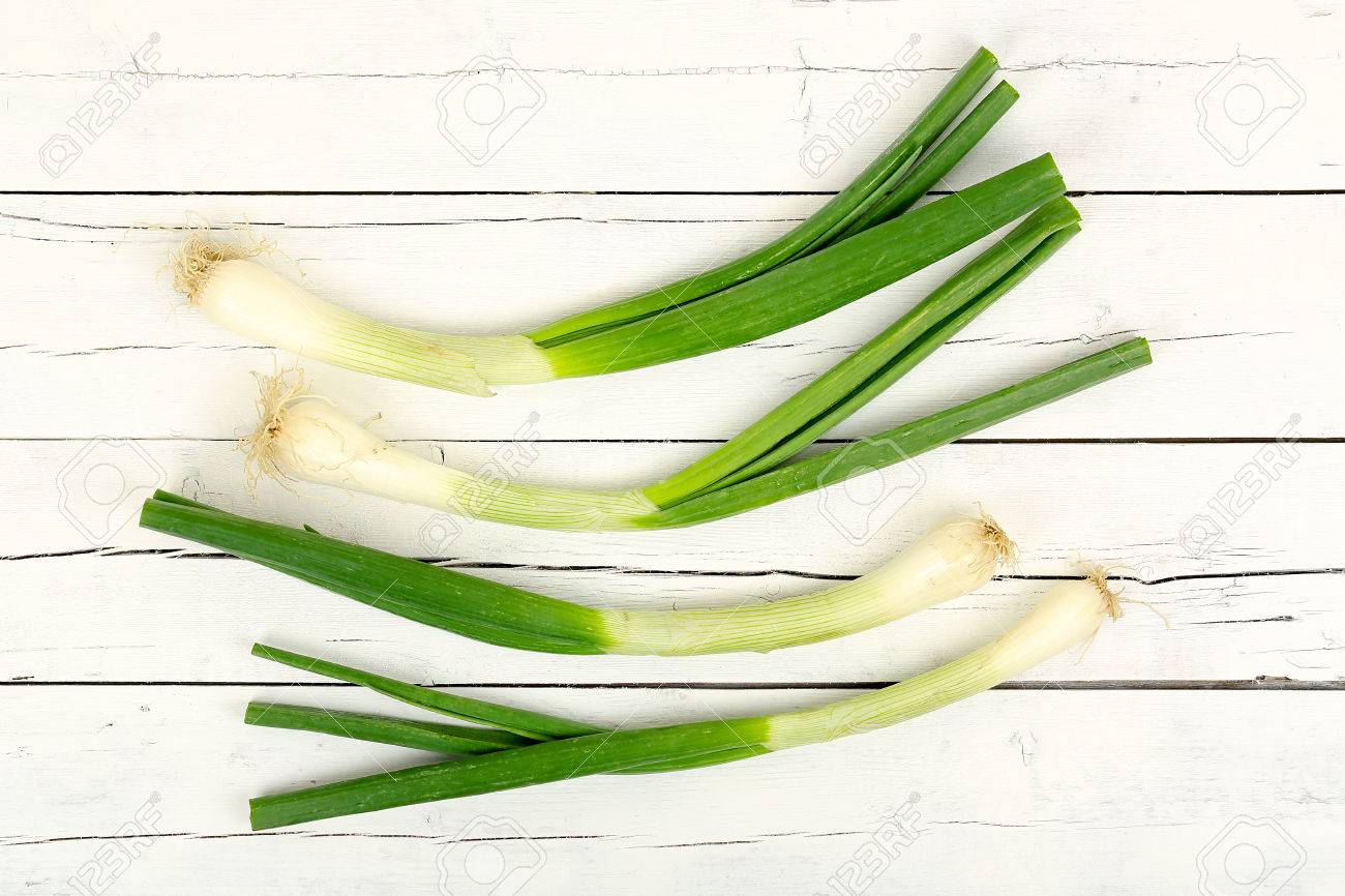 green onions or scallions on white wooden planks - 72712911