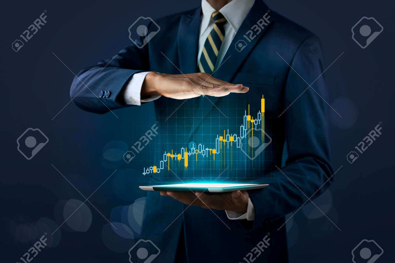 Business growth, progress or success concept. Businessman is showing a growing virtual hologram stock on dark tone background. - 165651209