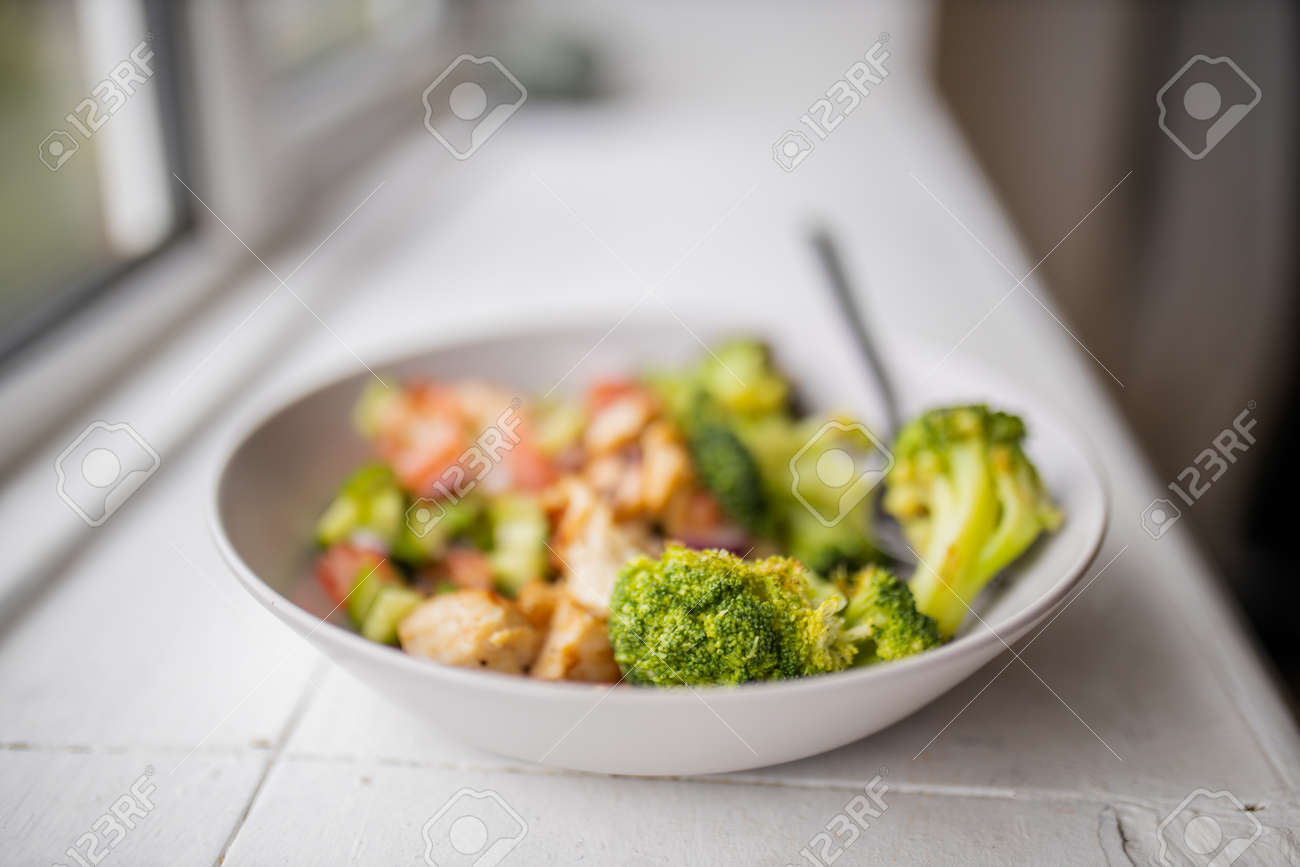 Broccoli and chicken salad on white bowl next to a window - 159347288