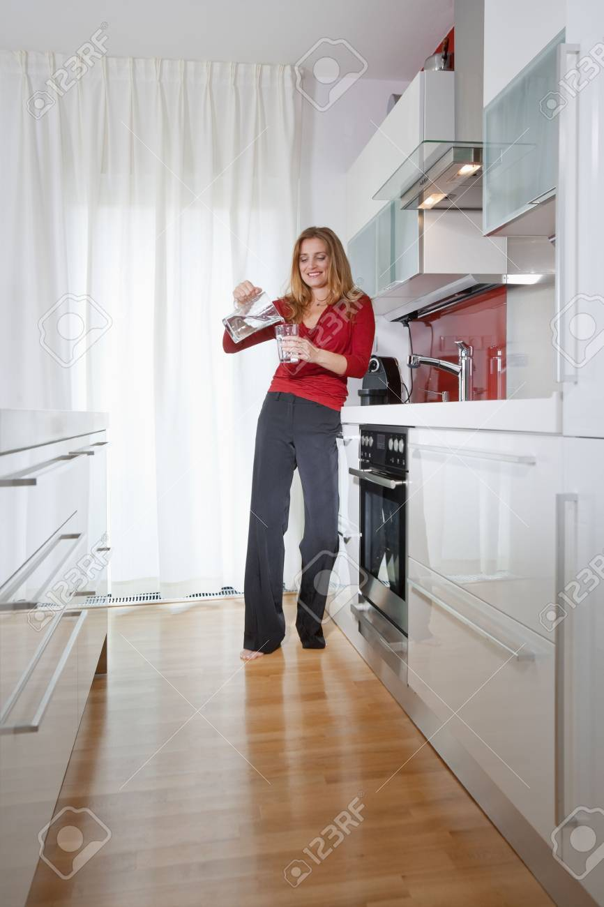 Young Beautiful Woman Standing In Modern Kitchen Interior Stock ...