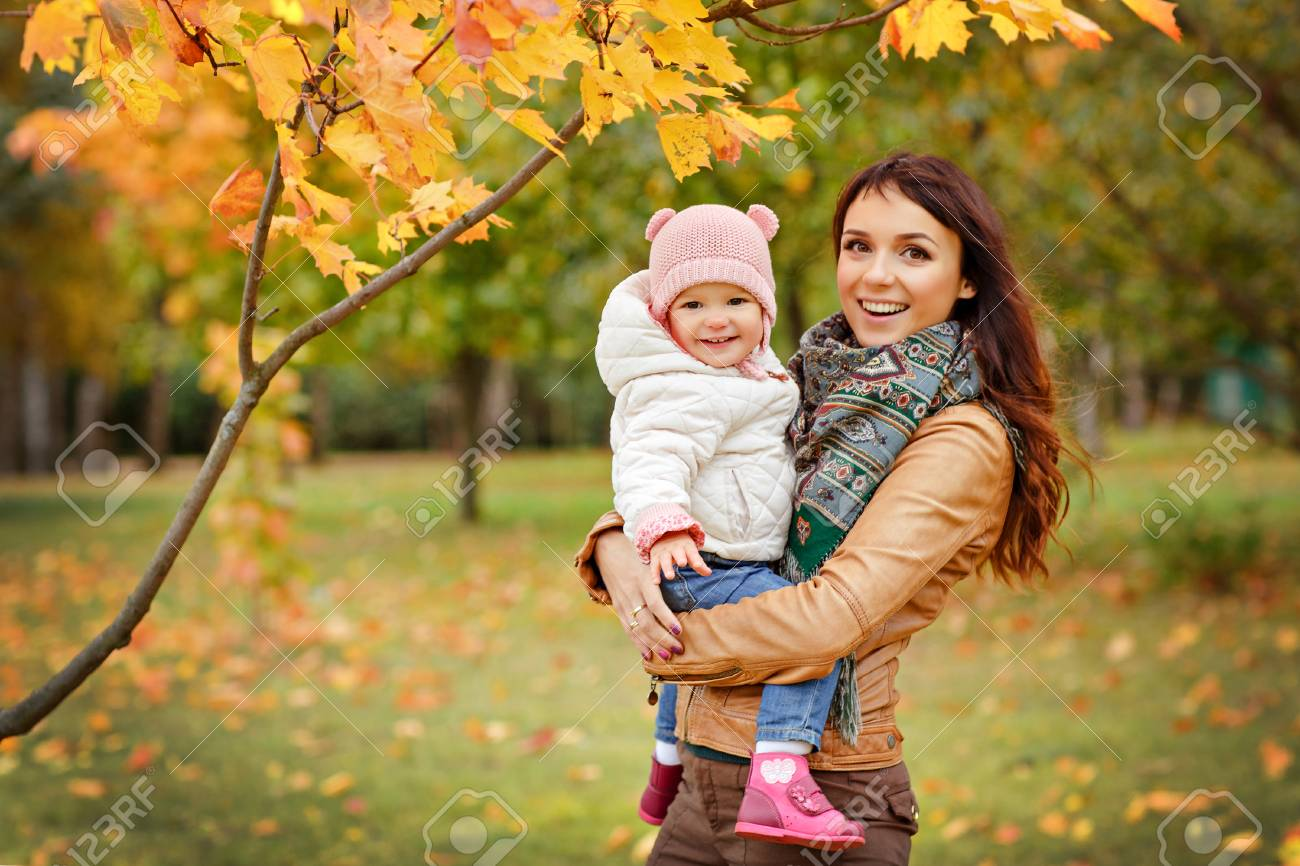 Stock Photo Very Charming Beautiful Brunette Mom In A Brown Jacket Holding A Little Girl Her Daughter And Smiles Happily On The Background Of Yellow