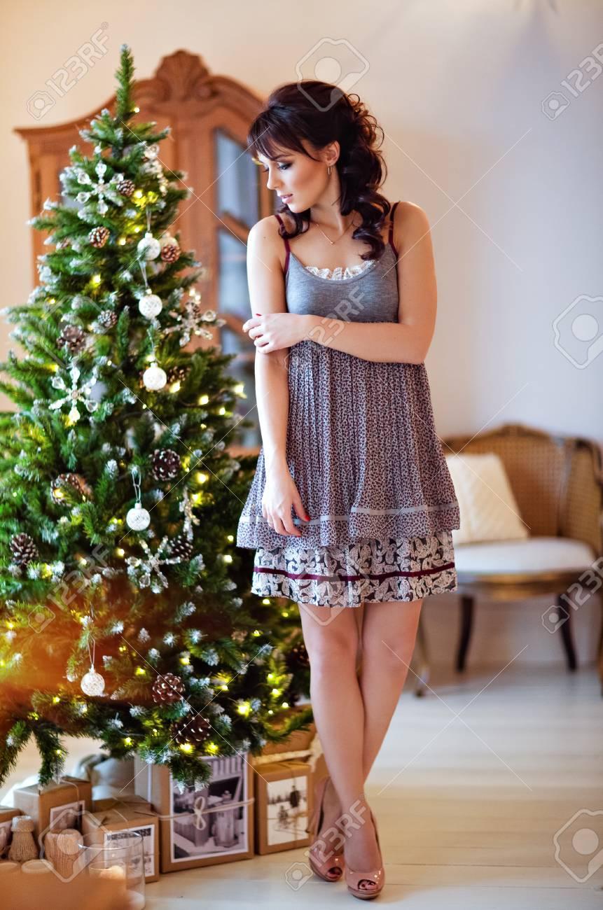d7d916614b Foto de archivo - Hermosa chica morena en un vestido gris de pie cerca de  árbol de Navidad
