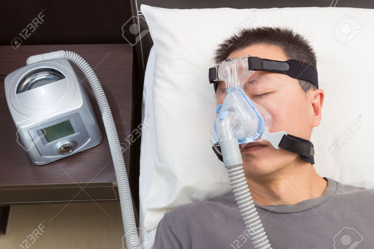 big sale 29e03 b96b8 Asian man with sleep apnea using CPAP machine, wearing headgear mask  connecting to air tube