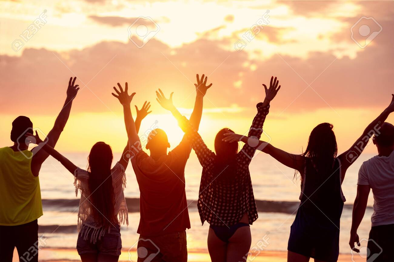 Silhouettes of six happy friends with raised arms stands against beautiful sunset sea beach - 131818591