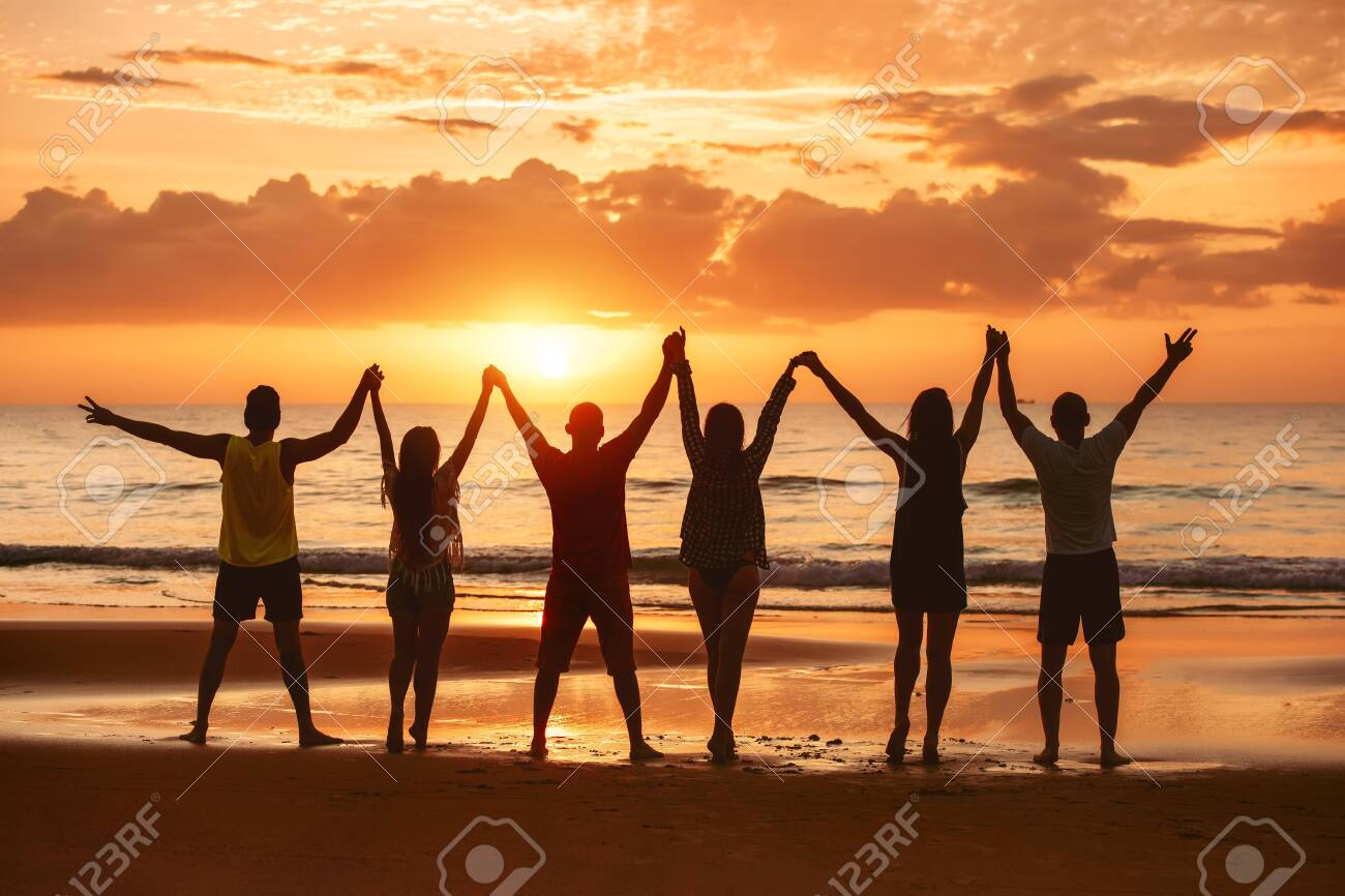 Group of happy friends are having fun with raised arms together at sea beach and enjoy sunset - 133808338