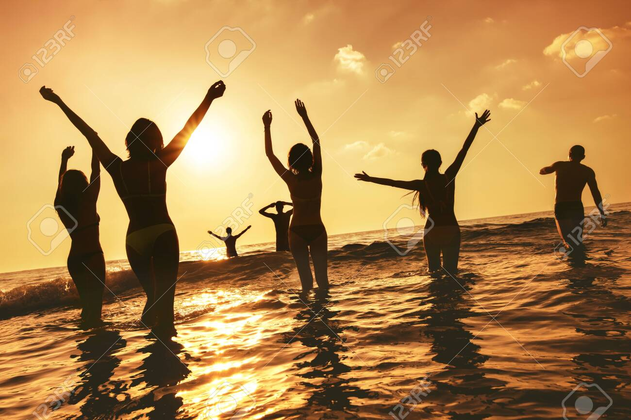 Big group of happy peoples stands at sunset sea beach. Silhouettes with raised arms - 140964025