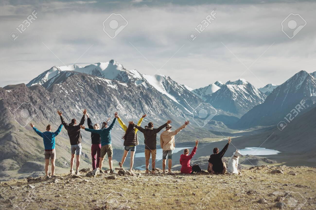 Big group of happy young hikers are standing with raised arms in mountains - 144664993