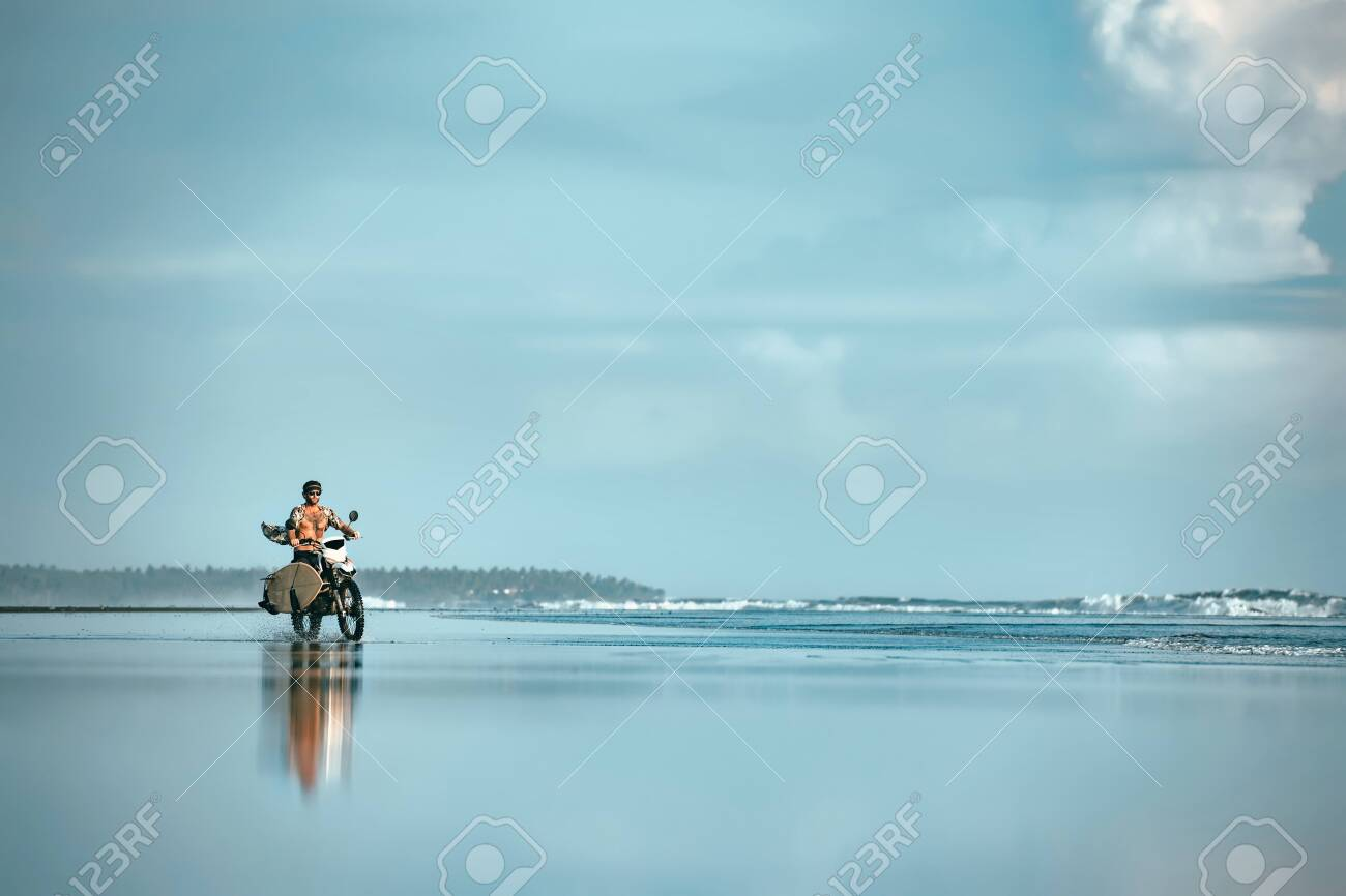 Authentic male surfer rides with surfboard on motorcycle at ocean beach. Real Bali surfing photo - 144779003