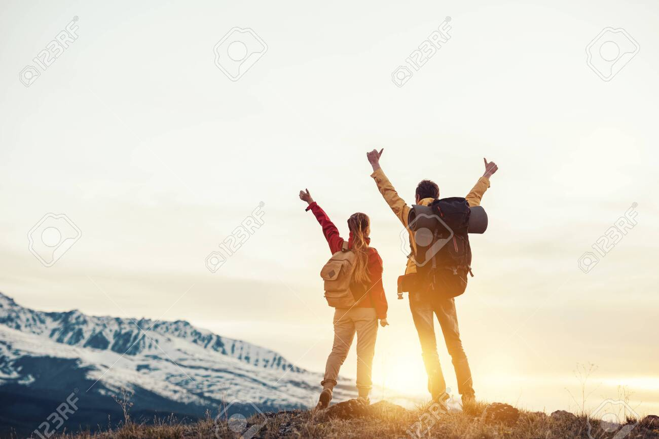 Two happy hikers with backpacks are standing with raised arms and looking at mountains and sunset - 145683326