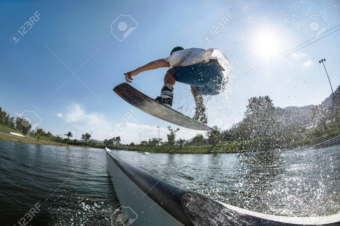Ma wakeboarder jumps at ramp at wake park - 147216045