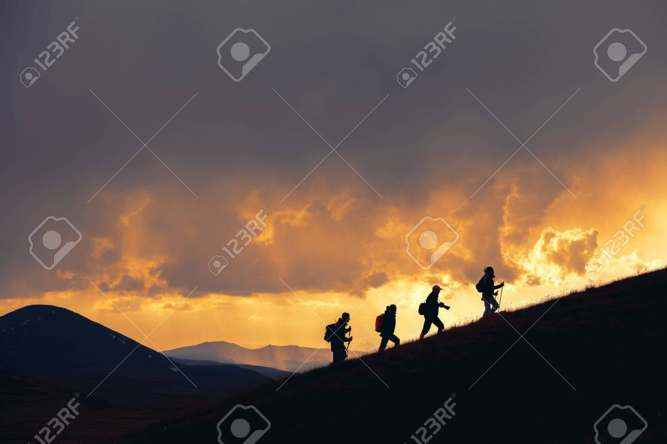 Group of unrecognizable hikers are walking at majestic sunset in mountains - 146037935