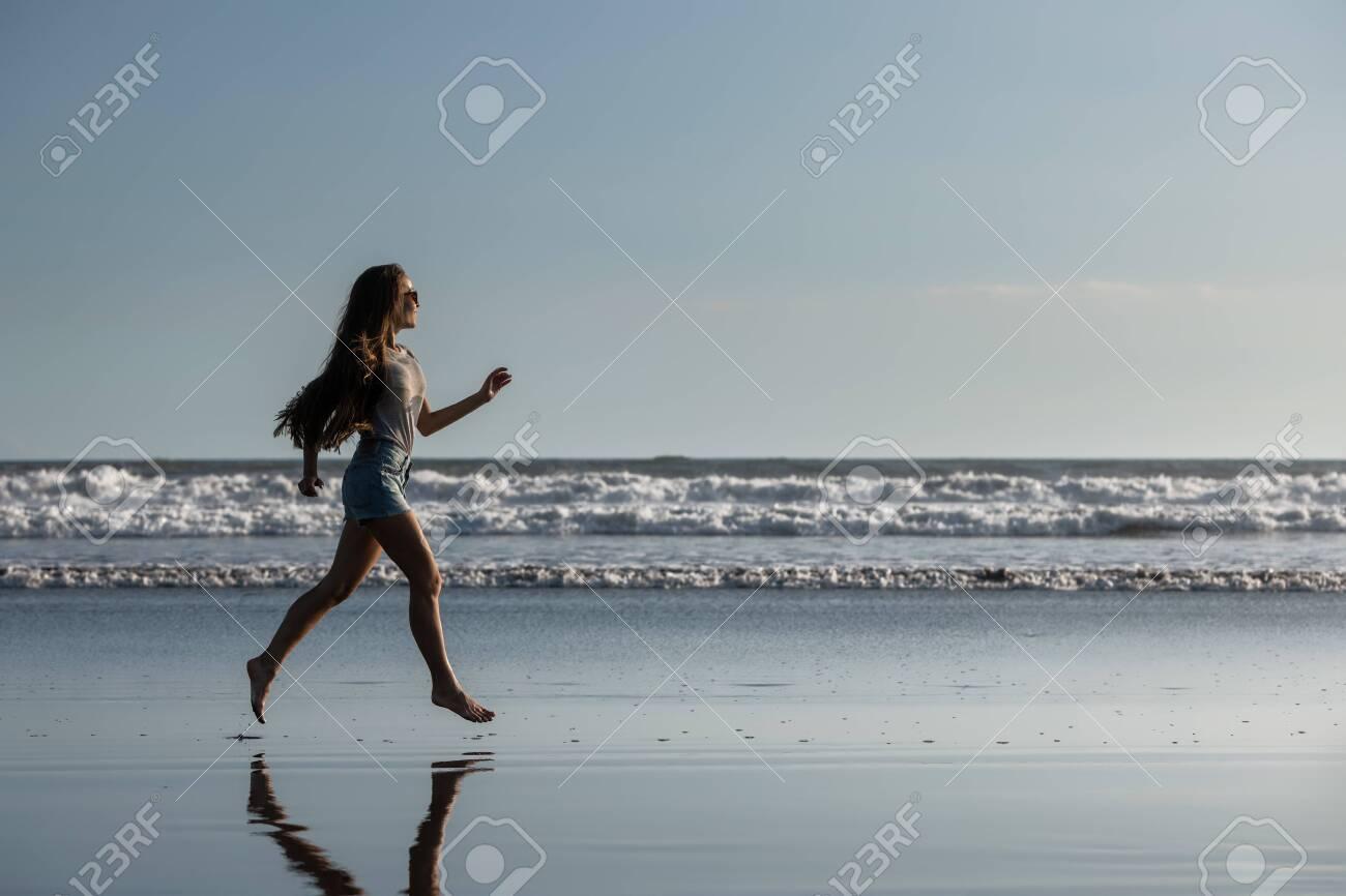 Happy beautiful girl runs alone at ocean beach - 146042713