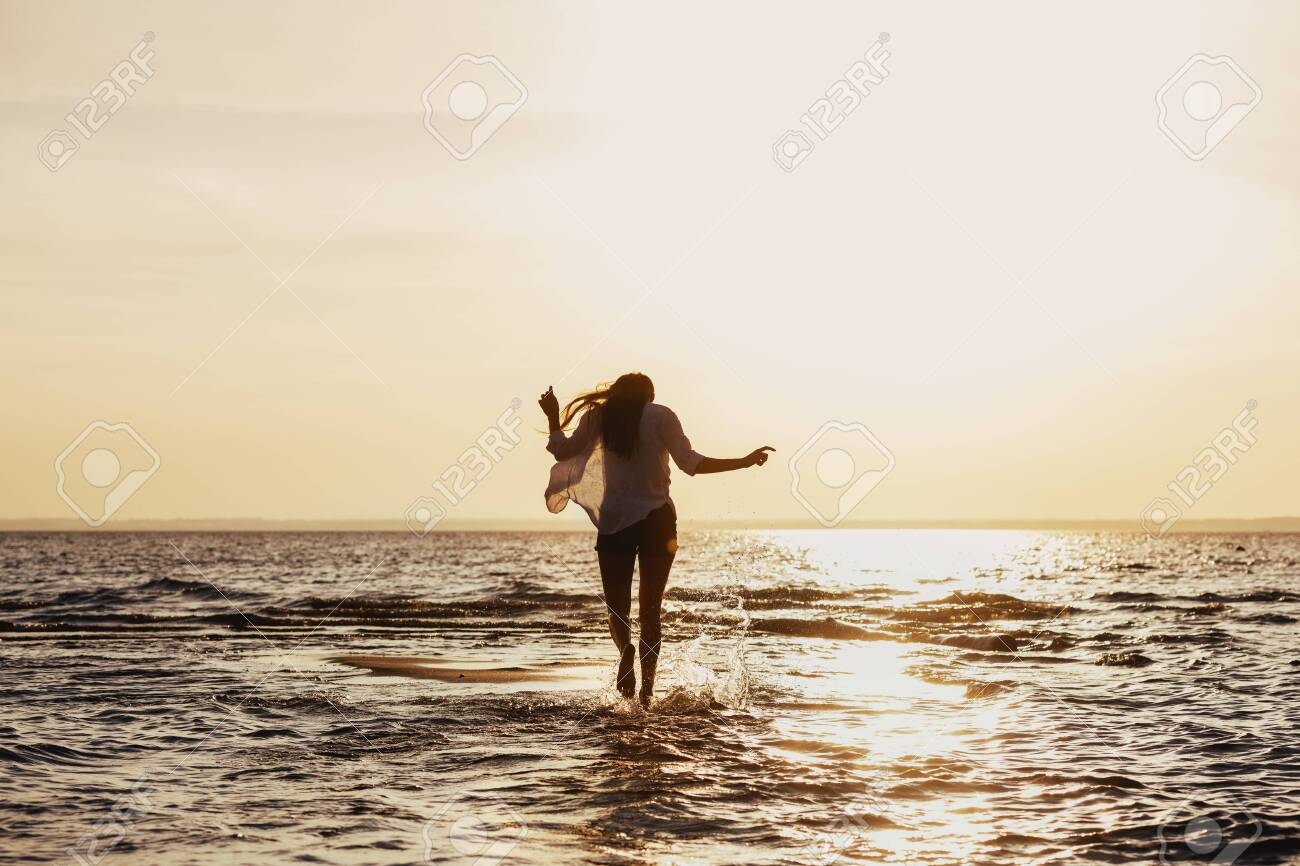Young slim girl walks by water at sunset beach - 146342079