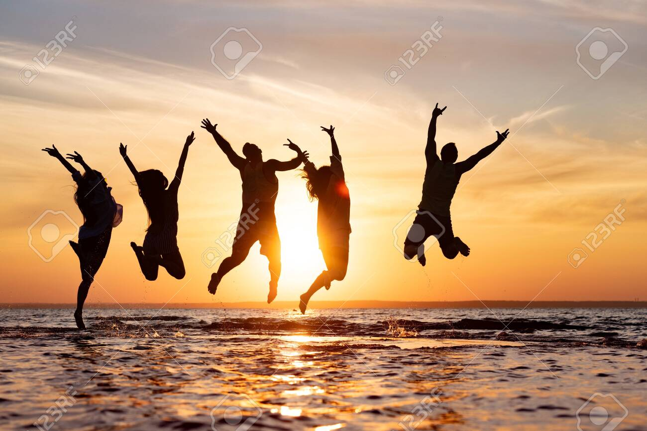 Five happy friends are having fun and jumping at sunset beach - 146421620