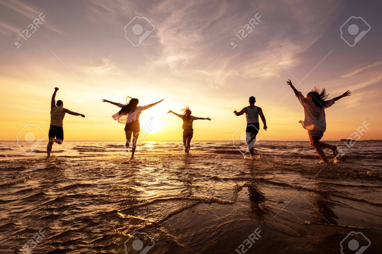 Five happy friends runs with raised arms at sunset beach - 146895621