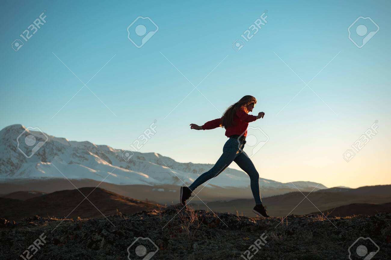 Slim sporty girl is walking in mountains at sunset time - 146896937