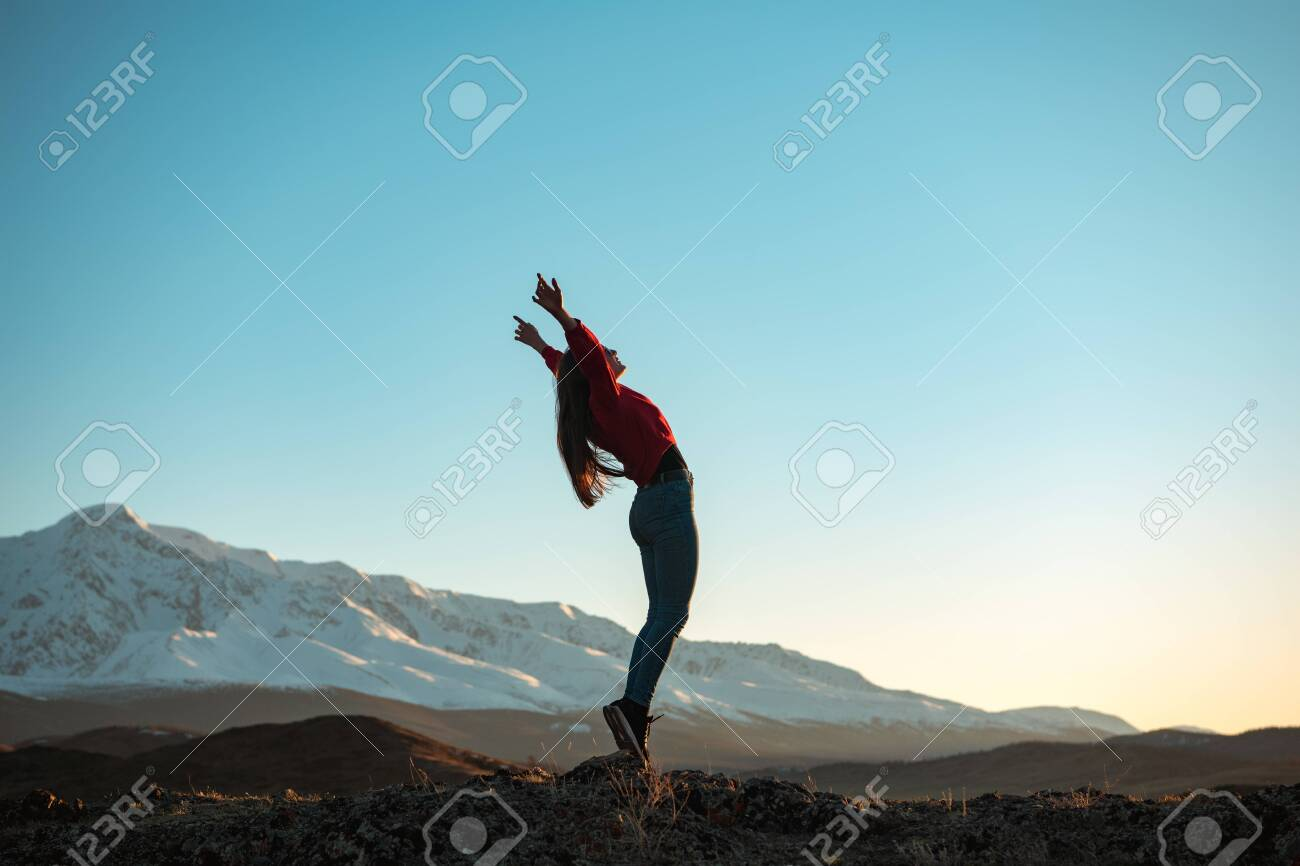 Young active girl is standing in winner pose in mountains at sunset or sunrise - 147026680