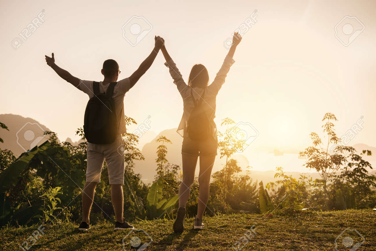 Two happy tourists are standing with raised arms at sea view point and enjoys sunrise - 150166705