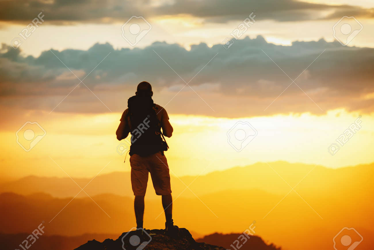 Unrecognized hiker stands with backpack on mountain top and enjoys sunset sky - 154759377