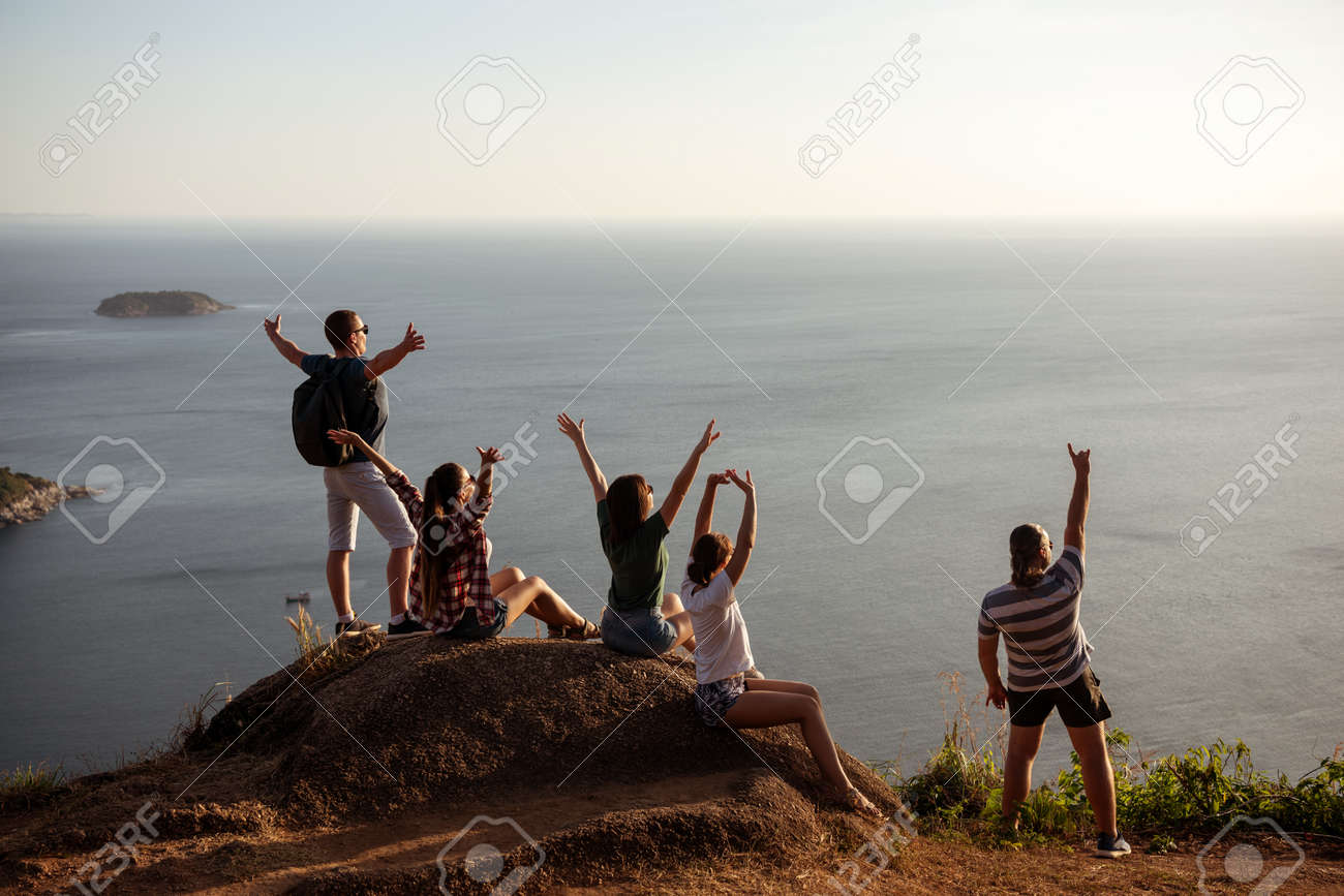 Five happy friends are having fun and enjoying sunset at sea view point - 154762141
